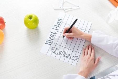 Photo for Cropped view of dietitian writing in meal plan at table with fruits - Royalty Free Image