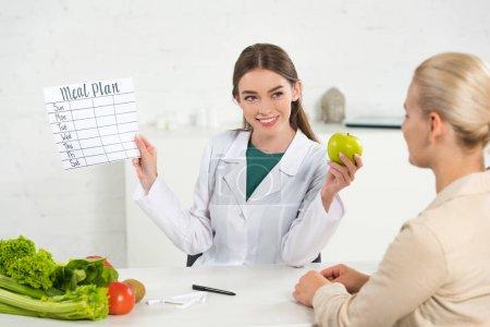 Photo pour Diététiste souriante en manteau blanc tenant le plan de repas et pomme et patient à table - image libre de droit