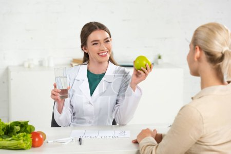 Photo for Smiling dietitian in white coat holding apple and glass of water and patient at table - Royalty Free Image
