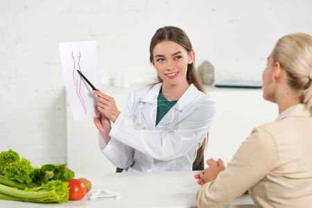 Photo for Smiling dietitian in white coat showing paper with perfect body image to patient - Royalty Free Image