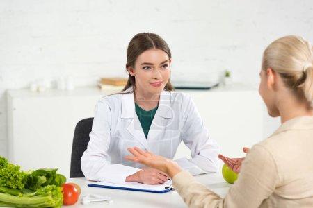 Photo pour Diététiste souriant en manteau blanc regardant le patient à la table - image libre de droit