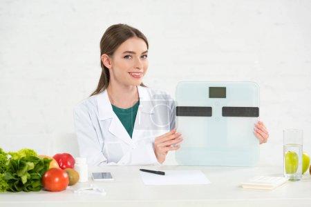 Photo pour Diététiste souriante en manteau blanc tenant des balances numériques sur le lieu de travail - image libre de droit