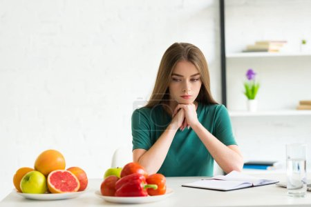 Photo for Sad woman sitting at table with fresh fruits and vegetables - Royalty Free Image