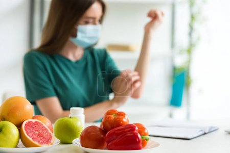 Photo for Selective focus of young woman in medical mask sitting at table with fruits, vegetables and pills and scratching arm at home - Royalty Free Image