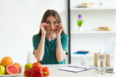 Photo for Girl with allergy wiping tears while sitting at table with fruits, vegetables and pills - Royalty Free Image
