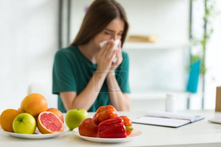 Photo for Selective focus of woman sitting at table with vegetables, fruits and pills and using napking while blowing nose - Royalty Free Image