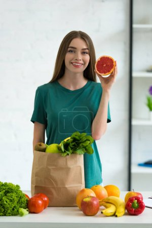 Photo for Smiling young woman standing near paper bag with fresh vegetables and fruits and holding cut grapefruit at home - Royalty Free Image