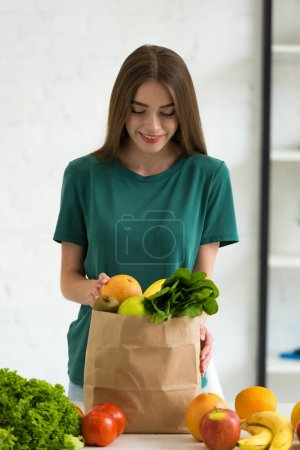 Photo for Smiling young woman standing near paper bag with fresh vegetables and fruits at home - Royalty Free Image