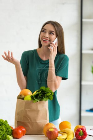 smiling girl standing near paper bag with fresh food and talking on smartphone at home