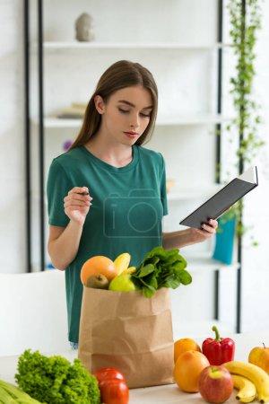 Photo pour Attrayant femme tenant stylo et manuel tout en se tenant près sac en papier avec des fruits et légumes frais - image libre de droit