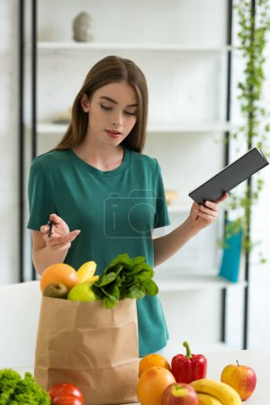 Photo for Attractive woman holding pen and textbook while standing near paper bag with fresh fruits and vegetables - Royalty Free Image