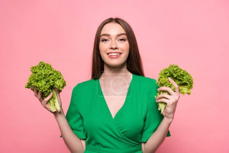 Photo for Front view of attractive young woman holding lettuce and looking at camera isolated on pink - Royalty Free Image