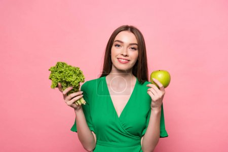 Photo for Front view of attractive young woman holding lettuce and apple and looking at camera isolated on pink - Royalty Free Image