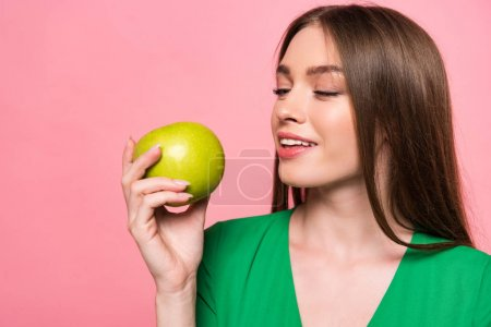 Photo for Attractive young woman holding green apple and smiling isolated on pink - Royalty Free Image