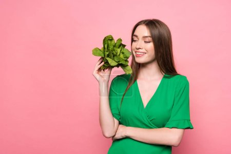 Photo for Smiling young woman holding spinach with closed eyes isolated on pink - Royalty Free Image