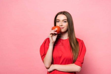 Photo pour Attrayant sourire fille tenant tomate et regardant caméra sur rose - image libre de droit