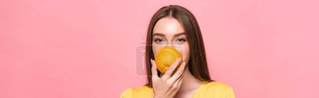 Photo for Panoramic shot of young woman eating orange and looking at camera isolated on pink - Royalty Free Image