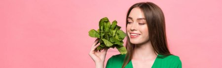 panoramic shot of attractive smiling girl holding spinach isolated on pink