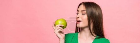 Photo for Panoramic shot of attractive smiling girl holding green apple isolated on pink - Royalty Free Image