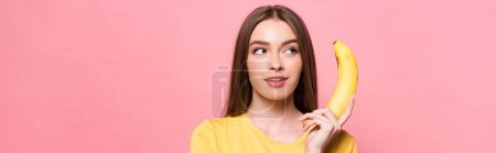 Photo for Panoramic shot of pensive attractive girl holding banana isolated on pink - Royalty Free Image