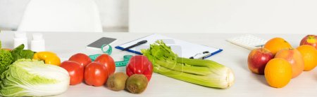 Photo for Panoramic shot of fresh fruits and vegetables, measure tape, clipboard, pen, calculator and smartphone with blank screen on table - Royalty Free Image