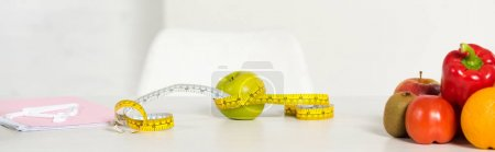 Photo for Panoramic shot of fresh fruits and vegetables, measure tape and textbook on table - Royalty Free Image