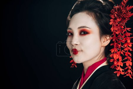Photo for Smiling beautiful geisha in black and red kimono and flowers in hair isolated on black - Royalty Free Image