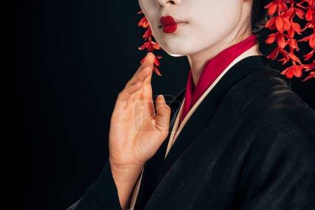 Photo pour Vue partielle de la belle geisha en kimono noir et rouge agitant la main isolé sur noir - image libre de droit