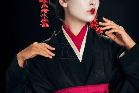 Photo pour Vue partielle de belle geisha dans le kimono noir et rouge gesticulant d'isolement sur le noir - image libre de droit