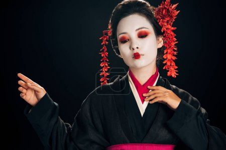 Photo pour Belle geisha en kimono noir et rouge et fleurs en cheveux geste isolé sur noir avec espace de copie - image libre de droit