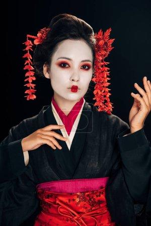 Foto de Geisha en kimono negro y rojo y flores en el pelo gesturing aislado en negro - Imagen libre de derechos