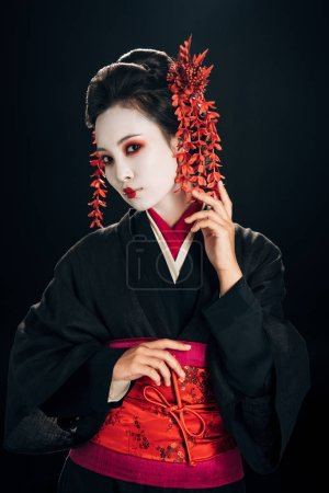 Photo pour Belle geisha en noir et rouge kimono et fleurs en cheveux isolés sur noir - image libre de droit