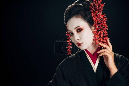 Foto de Hermosa geisha en kimono negro y rojo y flores en el pelo aislado en negro con espacio de copia - Imagen libre de derechos