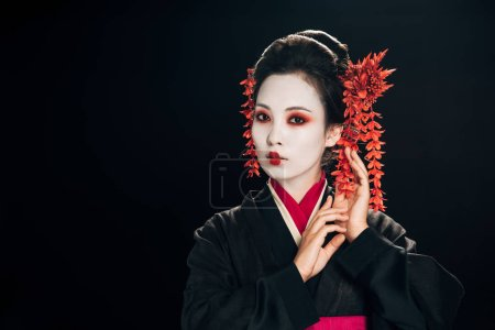 attractive geisha in black and red kimono and flowers in hair gesturing isolated on black