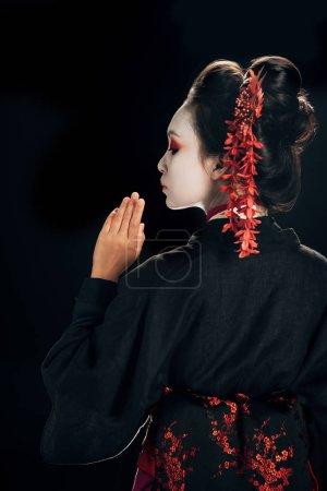Photo pour Vue arrière de belle geisha dans le kimono noir et rouge et les fleurs dans le cheveu d'isolement sur le noir - image libre de droit
