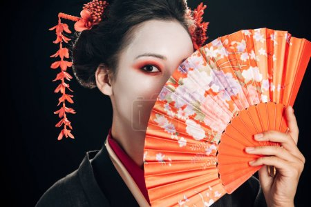 beautiful geisha with red flowers in hair holding traditional hand fan isolated on black
