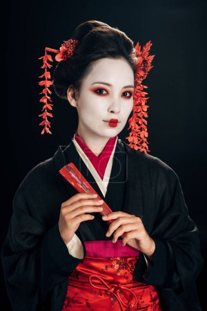 Photo for Beautiful geisha in black kimono with red flowers in hair holding traditional hand fan isolated on black - Royalty Free Image
