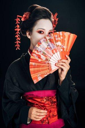 Photo pour Geisha en kimono noir avec des fleurs rouges dans les cheveux cachant visage derrière ventilateur traditionnel isolé sur noir - image libre de droit
