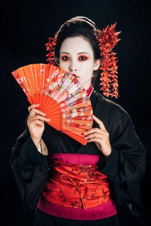 Photo pour Geisha en kimono noir avec des fleurs rouges dans les cheveux tenant ventilateur traditionnel isolé sur noir - image libre de droit