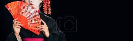 Foto de Vista parcial de hermosa geisha en kimono negro con flores rojas en el pelo sosteniendo ventilador de mano tradicional aislado en negro, tiro panorámico - Imagen libre de derechos