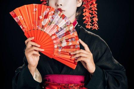 Foto de Vista parcial de hermosa geisha en kimono negro con flores rojas en el pelo sosteniendo ventilador de mano tradicional aislado en negro - Imagen libre de derechos