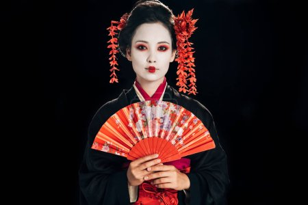 beautiful geisha in black kimono with red flowers in hair holding traditional hand fan isolated on black