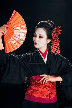 wunderschöne Geisha im schwarzen Kimono mit roten Blumen im Haar, die einen traditionellen Handfächer isoliert auf schwarz hält