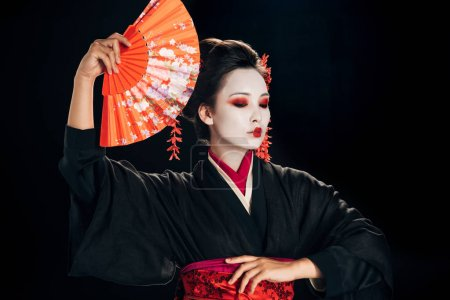 beautiful geisha in black kimono with red flowers in hair holding traditional orange hand fan isolated on black