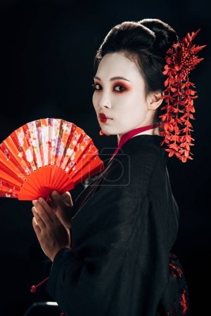 Photo for Geisha in black kimono with red flowers in hair holding traditional hand fan isolated on black - Royalty Free Image