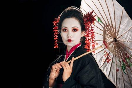 Photo pour Belle geisha en kimono noir avec des fleurs rouges dans les cheveux tenant parapluie asiatique traditionnel isolé sur noir avec espace de copie - image libre de droit