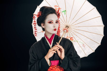 Photo for Beautiful geisha in black kimono with red flowers in hair holding asian umbrella isolated on black - Royalty Free Image