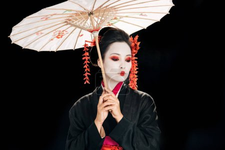 beautiful geisha in black kimono with red flowers in hair holding traditional asian umbrella and looking down isolated on black