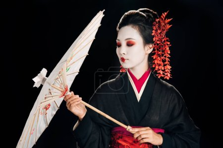 Photo for Beautiful geisha in black kimono with red flowers in hair looking at traditional asian umbrella isolated on black - Royalty Free Image