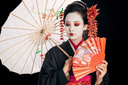 beautiful geisha in black kimono with red flowers in hair holding traditional asian umbrella and hand fan isolated on black